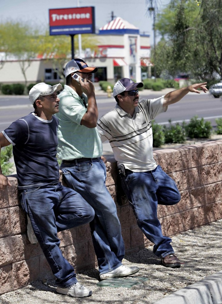 Jose Armenta, center, a 33-year-old illegal immigrant from Los Mochis, Sinaloa, Mexico, stands with his friend Vicente, left, while Julio Loyola Diaz of Juarez, Chihuahua, Mexico signals to motorists Wednesday in Phoenix. In the last two years, it is estimated that Arizona's illegal population has decreased by about 100,000, down to about 460,000.