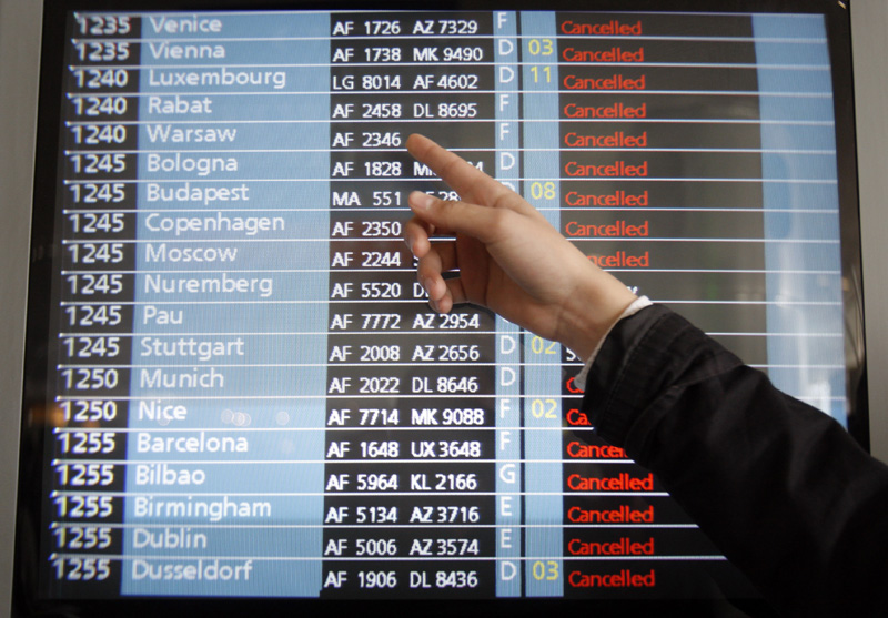 A passenger points to a flight information screen at Roissy Charles de Gaulle Airport outside Paris, as hundreds of commercial flights across northern Europe are canceled.