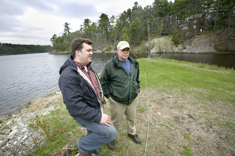 Ryan Tipping-Spitz, left, environmental organizer with the Maine People's Alliance, and Tim Conmee, a resident of Orrington and MPA member, walk along the Penobscot River, where erosion has been a problem because, the DEP says, groundwater is leaking into five tainted landfills.