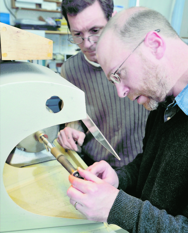 Goldsmith Deane Frank, left, instructs Ray Routhier on the correct way to polish the inside of a ring as he makes a wedding band at Brown Goldsmiths in Freeport.