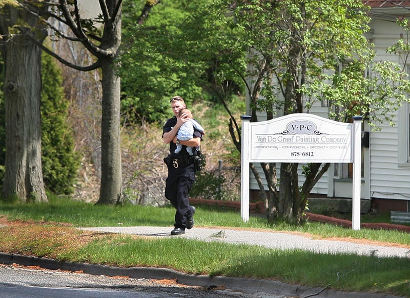 Eric Nevins, a Portland Police Department negotiator, carries a 5-month-old baby from an apartment during a police standoff Sunday on outer Forest Avenue.