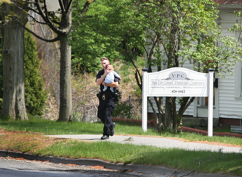 Eric Nevins, a Portland Police Department negotiator, carries a 5-month-old baby from an apartment during a police standoff on outer Forest Avenue in Portland on Sunday.