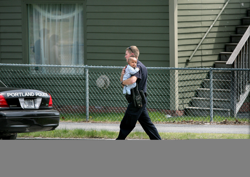 Eric Nevins, a Portland Police Department negotiator, carries a 5-month-old baby to family members after being removed from an apartment during a police standoff on outer Forest Avenue in Portland on Sunday.