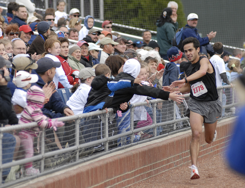 Louie Luchini of Ellsworth, the first finisher of Sea Dogs Mother's Day 5K gets high fives from spectators as he approaches the finish line today