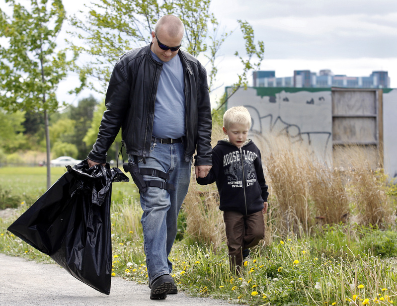 Josh Spicer of West Bath walks with his five year-old son Ryan during an open-carry trash pickup at Back Cove in Portland today.
