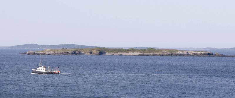 A fishing boat passes by Ram Island in Casco Bay on Monday. Ram Island was the destination of Irina McEntee and Carissa Ireland while kayaking on Sunday. It was the last place they were seen alive by a caretaker on a nearby island and McEntee's parents, who could see from Peaks Island that the girls had made it to the island.