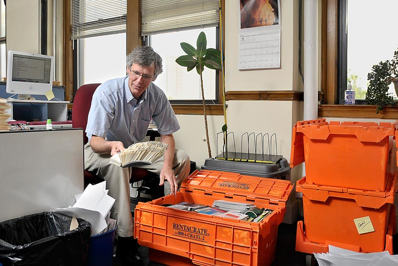 John Richardson, a reporter with The Portland Press Herald, has to decide what to save and what to throw out as he packs his belongings for the editorial staff's move to One City Center.