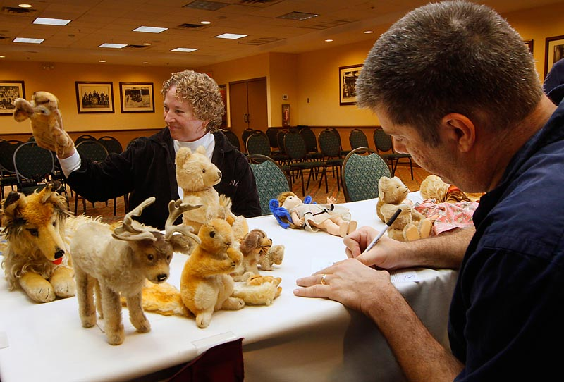 Willow Femmechild of Portland plays with one of her puppets Sunday while Bruce Zalkin estimates the value of her collection.