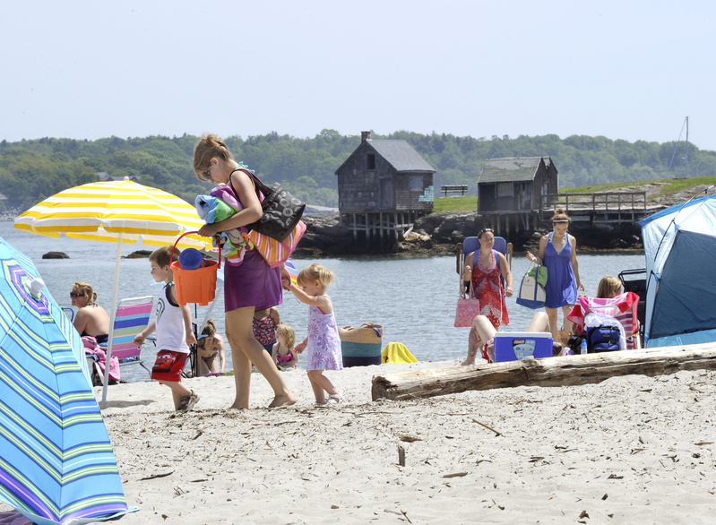 Windham residents Erin Hansen and her children, Reid, 4, and 2-year-old Grace, escape the heat by enjoying a cool ocean breeze at Willard Beach in South Portland.
