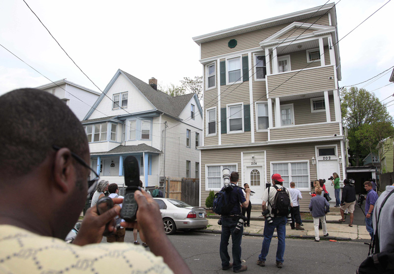 A local resident, left, and members of the media photograph a house in Bridgeport, Conn., today. Faisal Shahzad lived in the building's second floor apartment.