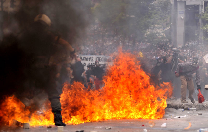 Riot police clash with demonstrators in central Athens today. Greek fire officials say three people died in a blaze that broke out at an Athens bank during rioting over government austerity measures. Angry protesters also tried to storm parliament, hurled Molotov cocktails at police and torched buildings.