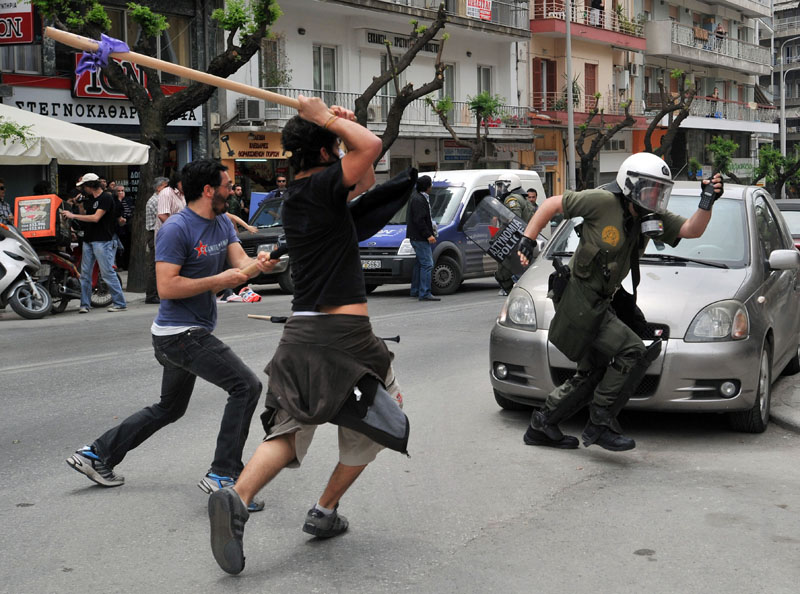 A riot policeman runs from angry protesters in the northern Greek port city of Thessaloniki today.