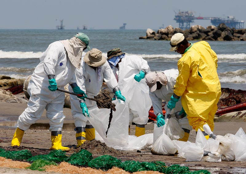 """Workers shovel oil from the Deepwater Horizon spill off the Louisiana coast Monday. Last weekend, Interior chief Ken Salazar said the government could intervene aggressively if BP didn't deliver, but Coast Guard Adm. Thad Allen said Monday, """"That's more of a metaphor."""""""