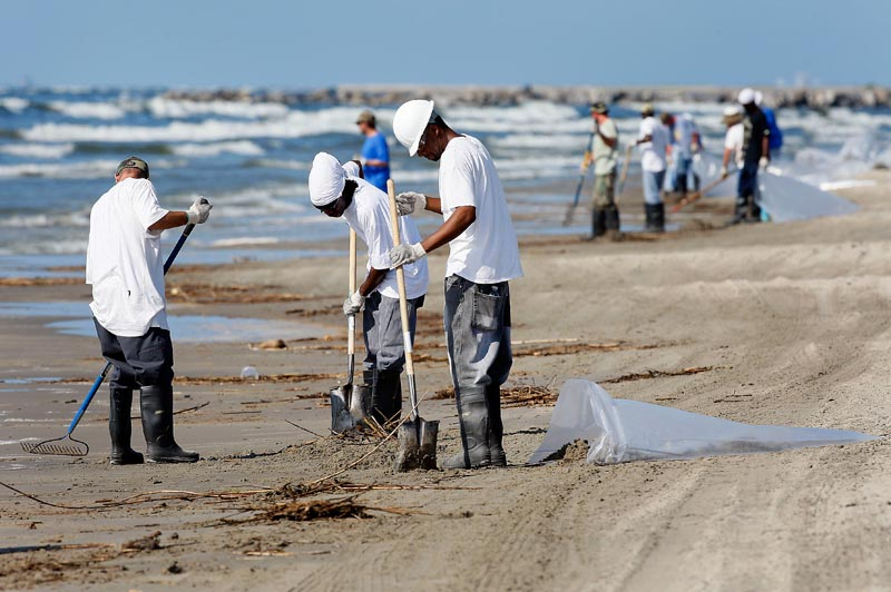 Workers collect oil and debris that washed up onto a beach in Grand Isle, La., Saturday. Oil from last month's Deepwater Horizon oil rig explosion in the Gulf of Mexico has started drifting ashore along the Louisiana coast.