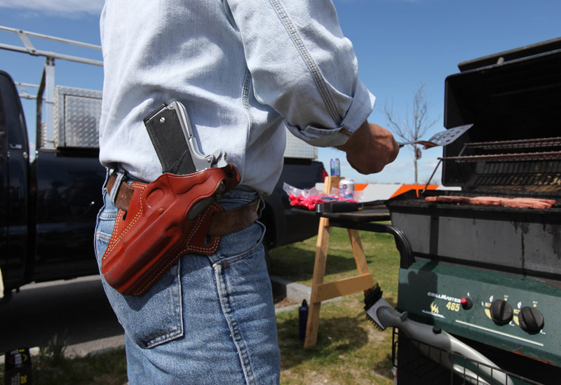 """A gunowner wears a .45-caliber semi-automatic pistol as he barbecues at the first """"open-carry"""" gun-rights rally on April 25 at Back Cove. Portland used to put limits on carrying guns openly in public, but the state Legislature later prohibited communities from regulating firearms."""