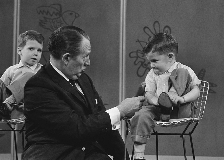 """In this April 5, 1962, file photo, TV personality Art Linkletter talks with 4-year-old Ronnie Glahn, who shows Linkletter his idea of how bad guys look, on Art's TV show """"People Are Funny."""" Childhood,Communication,Fame,Holding,Microphone,Sitting"""
