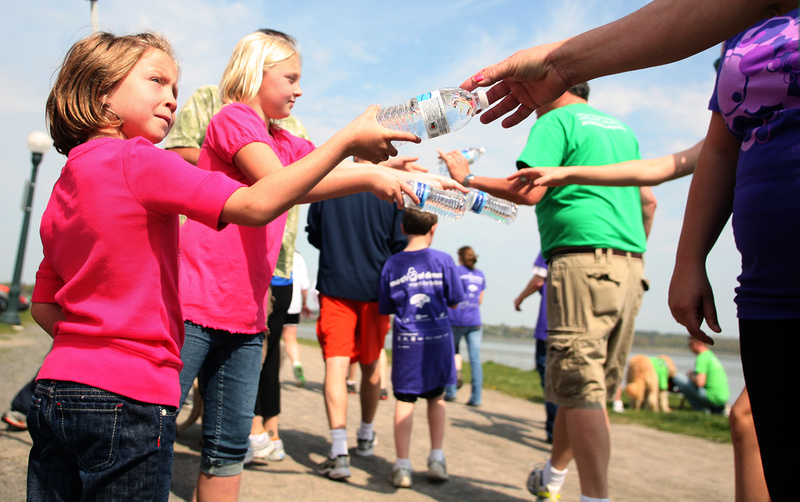 Kayla Rairdon, 6, left, and her sister Hannah, 9, of Westbrook hand out water to walkers at a water station along the Back Cove during the March of Dimes March for Babies in Portland on Sunday.
