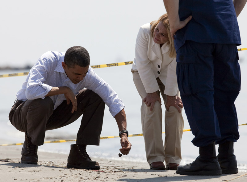 """President Barack Obama, left, picks up a """"tar ball"""" as LaFourche Parish president Charlotte Randolph, center, and U.S. Coast Guard Admiral Thad Allen, National Incident Commander for the BP Deepwater Horizon oil spill, look on during a tour of areas impacted by the Gulf Coast oil spill today in Port Fourchon, La."""
