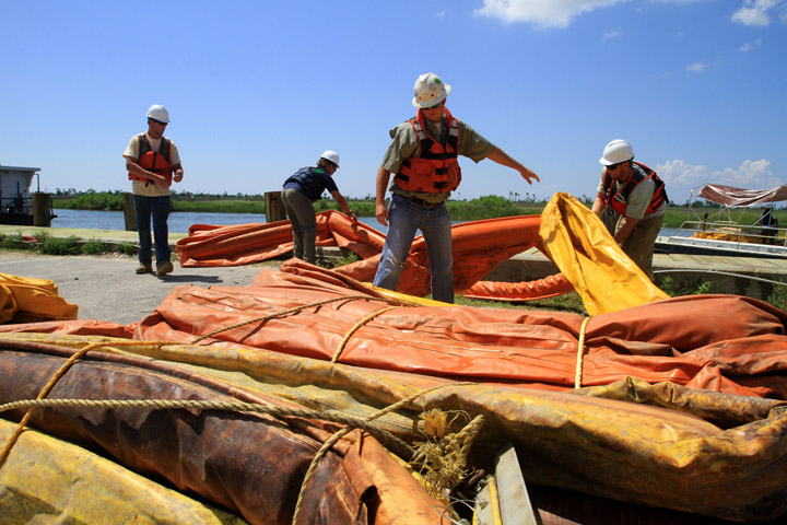 Workers with United States Environmental Services work with boom at Bayou Caddy in Hancock County as efforts continue to contain the oil spill in the Gulf of Mexico.