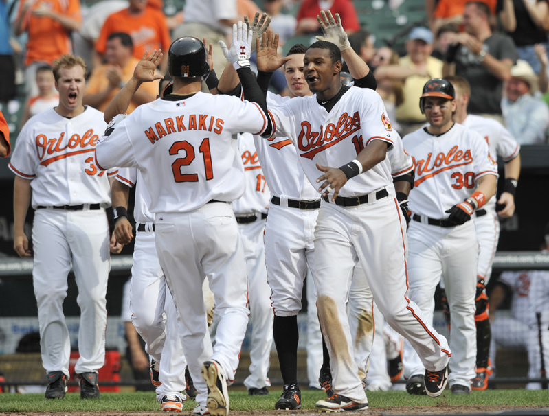 The Associated Press Nick Markakis of the Orioles is greeted at home after scoring the winning run in a 3-2 decision over the Red Sox in 10 innings Sunday. It's Baltimore's first home three-game sweep of Boston in 36 years.