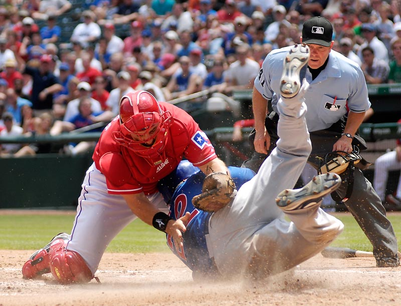 Rangers catcher Matt Treanor tries to tag Xavier Nady of the Cubs as umpire Jerry Meals watches in the sixth inning Sunday at Arlington, Texas. Nady was safe. The Cubs won 5-4.