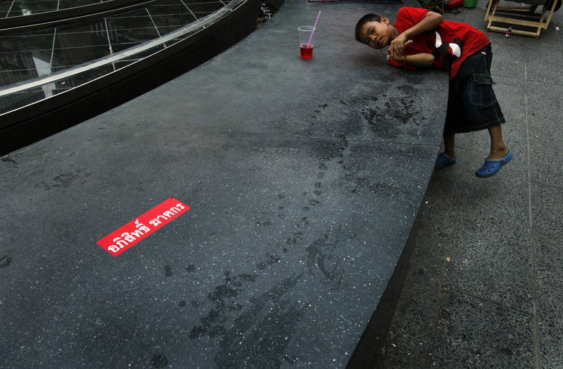 Despite the violence, a boy plays outside a closed upscale shopping mall in downtown Bangkok on Sunday.