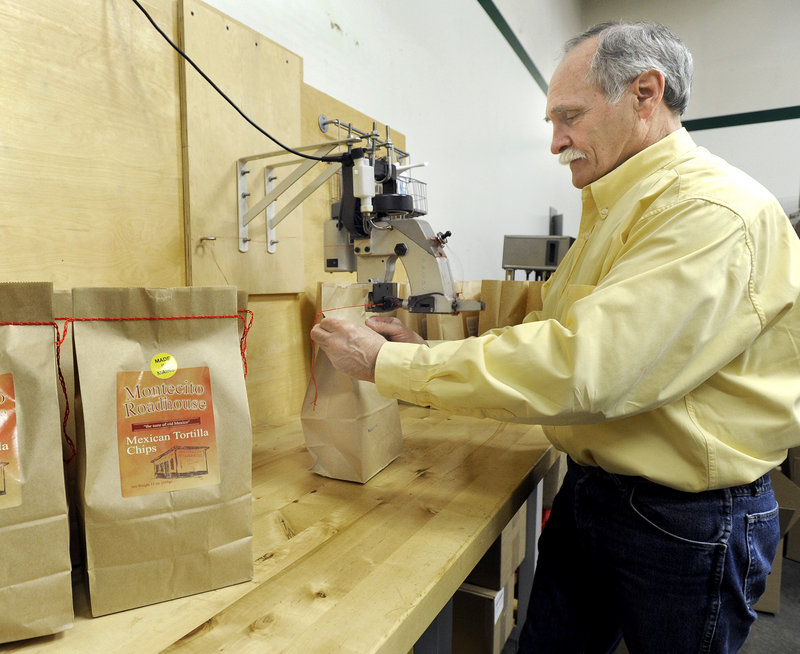 Scott Rehart, owner of Montecito Roadhouse Inc. in Portland, applies the trademark red stitching to a bag of tortilla chips.