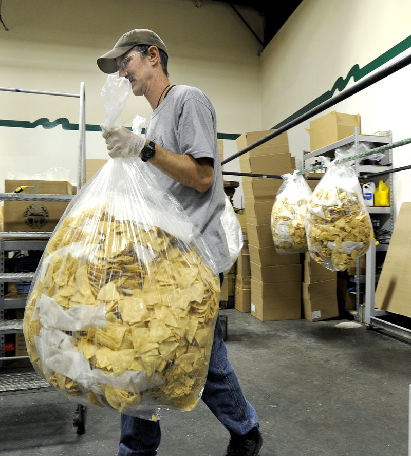 Larry Cook totes a bag of tortilla chips for sorting and bagging at Montecito Roadhouse Inc. in Portland.