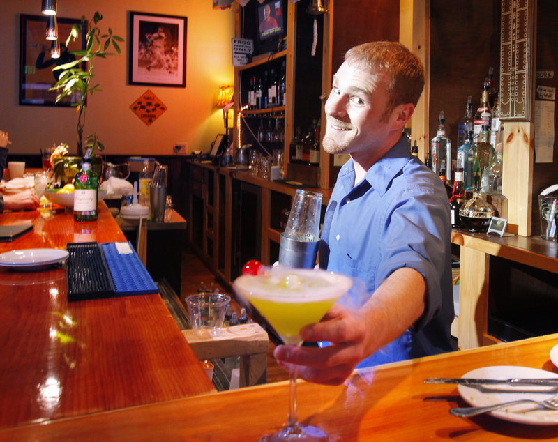 At the Frog & Turtle pub in Westbrook, bartender Evan Walsh displays a Swamp Martini, one of the pub's signature drinks.