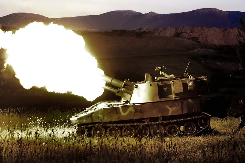 """Two self-propelled howitzers fire shells during a training exercise Thursday night in Thiva, Greece. Greece's defense minister promised """"colossal"""" cuts in military operating costs to help the country emerge from its financial crisis and speed plans to modernize the armed forces."""