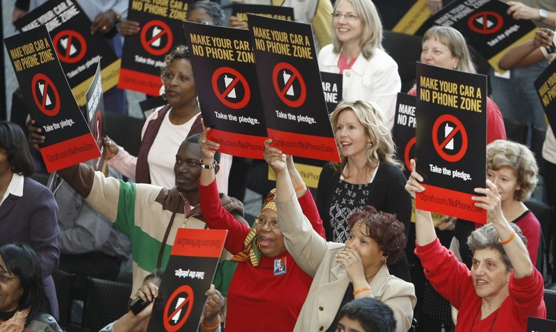 "Supporters of of driving without cell phones hold placards during a rally in Detroit. Oprah Winfrey dedicated her Friday show to distracted driving and wants America's drivers to declare their cars ""No Phone Zones."""