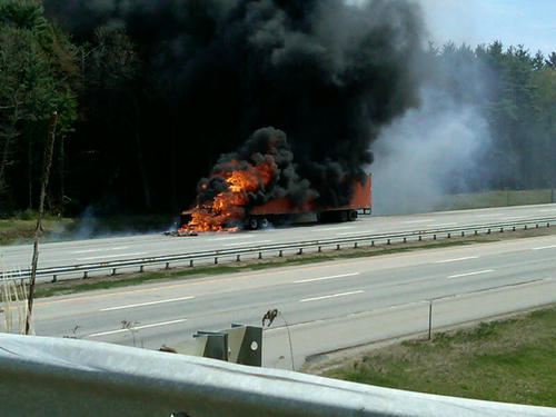"""A tractor-trailer burns on the turnpike. """"It's just the worst timing – a Friday at 1:30 in the afternoon,"""" said state police Trooper Gavin Hager."""