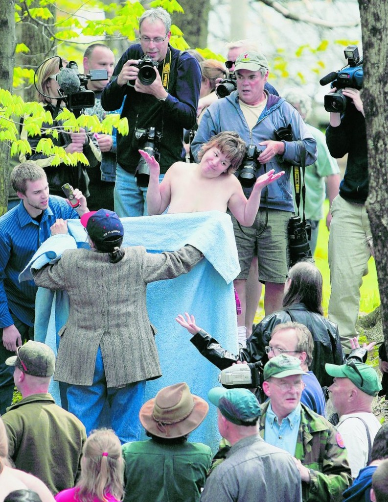 University of Maine at Farmington student Andrea Simoneau shrugs as Elaine Graham shields Simoneau's breasts during a topless protest Friday in Farmington. The demonstration called attention to a perceived double-standard that makes it acceptable for men, but not women, to be topless in public.