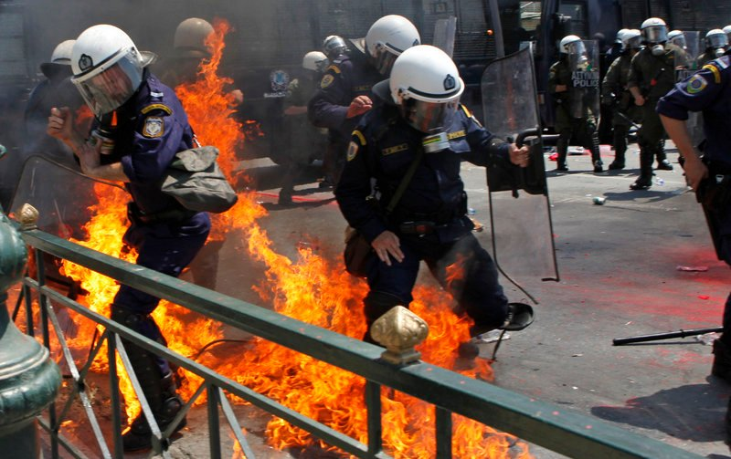Greek riot police are set on fire by protesters throwing Molotov cocktails in Athens on Saturday. Seven officers and two demonstrators were injured in the rioting.