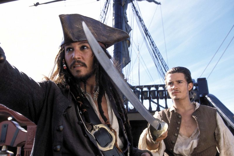 "Capt. Jack Sparrow (Johnny Depp, left) and Will Turner (Orlando Bloom, right) are shown in a scene from ""Pirates of the Caribbean: The Curse of the Black Pearl."" An 18-year-old woman has pleaded not guilty to breaking into Bloom's home."