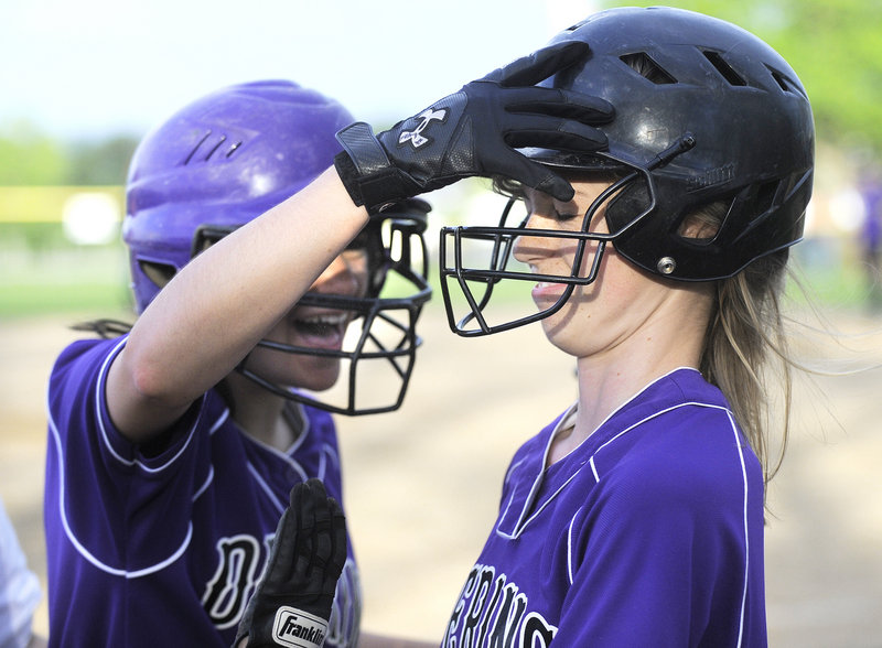 Nicole Mason of Deering gets a pat on the helmet from Jen Lynch after scoring the go-ahead run in the bottom of the sixth inning.