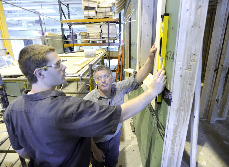Carpentry instructor Frank Kehoe, right, works with Jonathan Webster as Portland Arts and Technology High School students construct a