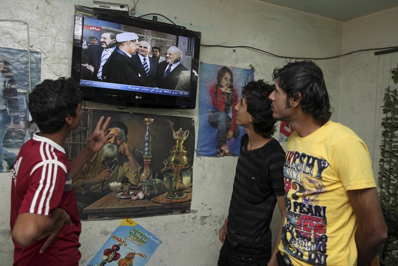 Iraqi men gather in a cafe Tuesday in Baghdad's Shiite stronghold of Sadr City to watch a news conference announcing the formation of a Shiite political coalition. The nation's election on March 7 produced no clear winner.