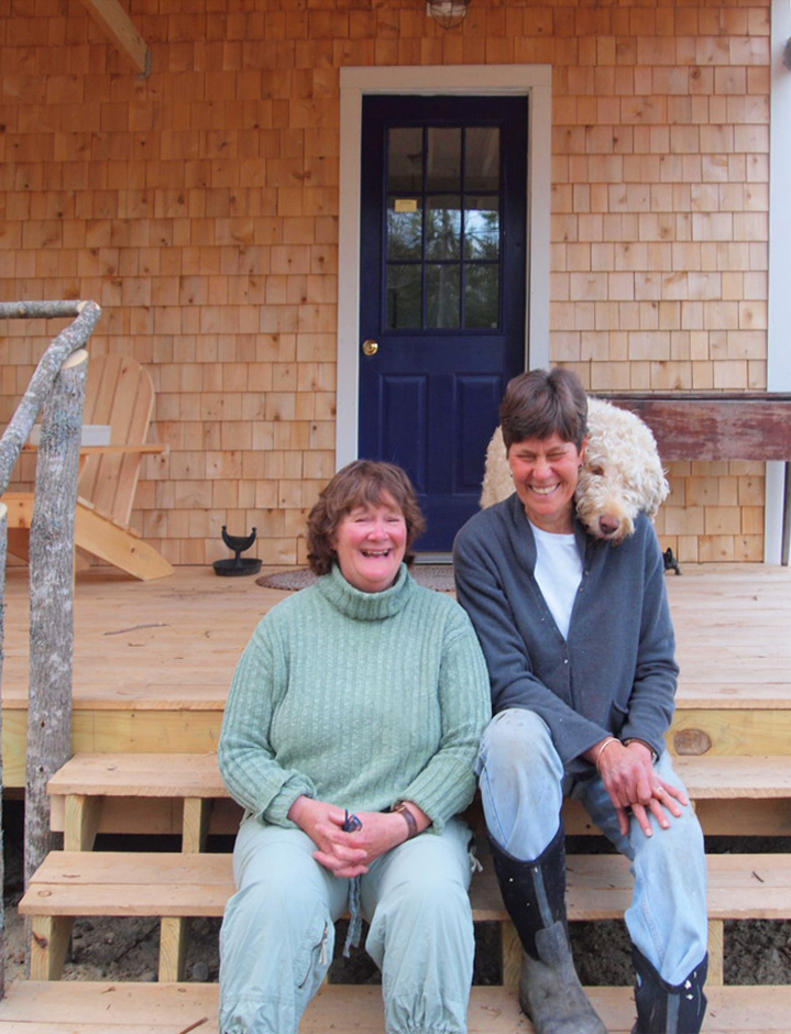 Partners Deede Montgomery and Kathy Heye, with Charlie the dog, sit on the steps of Bessie's Farm Goods, which they built at 33 Litchfield Road in Freeport. The store opened Monday and will celebrate with a grand opening and sale of about 600 perennials this weekend.