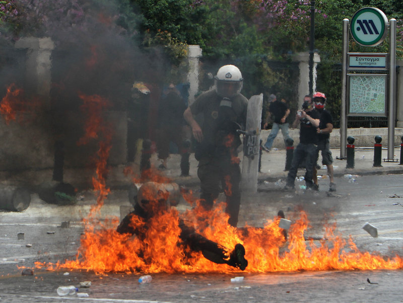A riot officer is engulfed in flames from a firebomb thrown by protesters Wednesday in Athens. Demonstrators hurled stones at police, who responded with tear gas, as tens of thousands of Greeks took to the streets to protest harsh new cuts aimed at saving their country from bankruptcy.