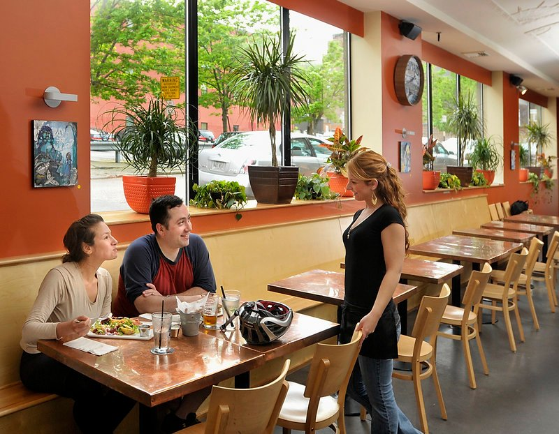 Paige Vashon, a server at Nosh Kitchen Bar, asks customers Luisa Barragan and Jonathan Koerber how their meal tastes after they stopped in for a quick lunch while bike touring in Portland.