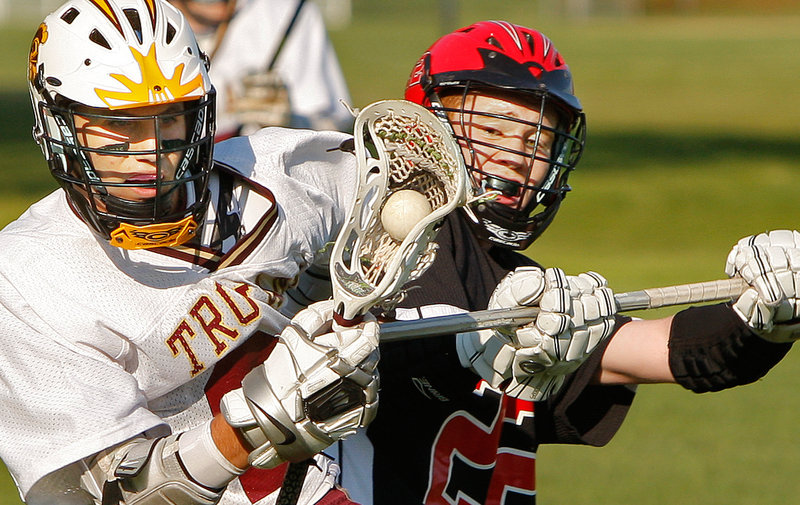 Peter Moore of Scarborough, right, attempts to dislodge the ball from Josh Cyr of Thornton Academy during their schoolboy lacrosse game Wednesday. Scarborough earned a 6-4 victory at Saco.