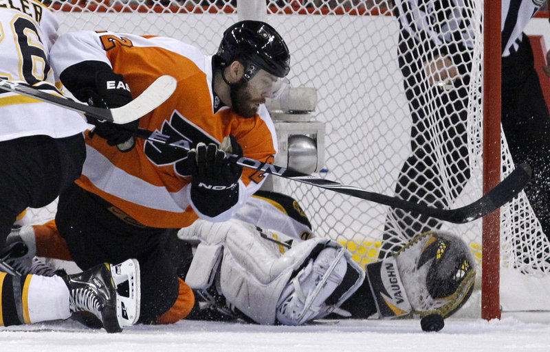 Ville Leino of the Flyers looks for the puck as Bruins goalie Tuukka Rask tries to cover the corner with his glove hand while sprawled in the goal. Rask had 34 saves in Boston's 4-1 win.