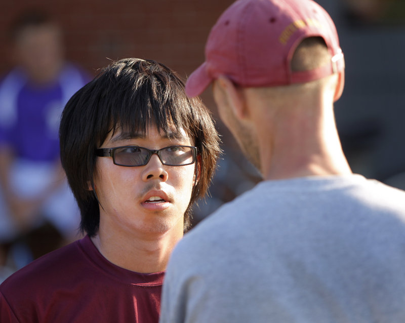 """Yide """"Clarence"""" Tan, talking with Coach Andrew Carlson, plays tennis for Thornton Academy. Tennis is popular with international students because they already know the sport."""