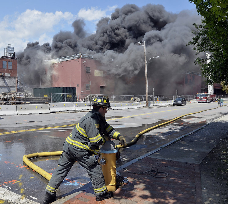 A Portland firefighter turns on a hydrant at Franklin and Fore streets to add water to the fire at the former Jordan's Meats building Thursday. About 100 firefighters battled the blaze, which broke out around 1:30 p.m.