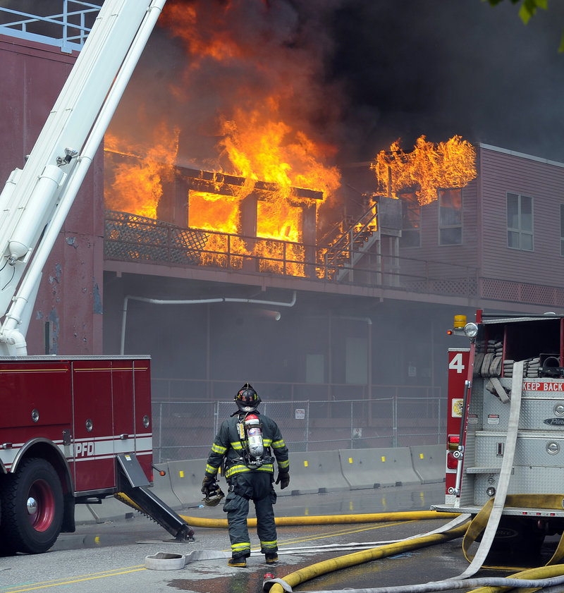 A Portland firefighter on Fore Street observes flames at the former Jordan's Meats plant Thursday. The blaze is being investigated by Portland's police and fire departments, the state Fire Marshal's Office and the federal Bureau of Alcohol, Tobacco, Firearms and Explosives.