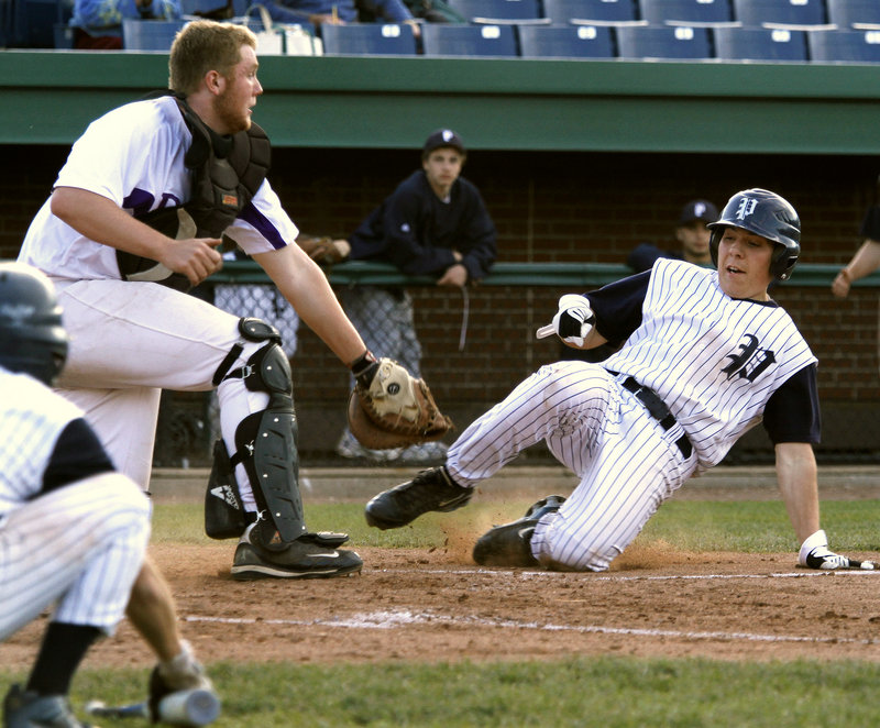 Rudy DiMillo of Portland is tagged out at the plate Thursday by Deering catcher Pat Bride while trying to score in the fifth inning of Portland's 8-7 victory at Hadlock Field. The Bulldogs are 4-1 and dropped Deering to 4-2.