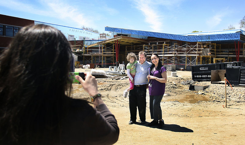 Julie Lannon photographs Will Leschey with his daughter Grace and her kindergarten teacher, Juanita DeWitt, during a tour of the new Ocean Avenue Elementary School in Portland on Friday.