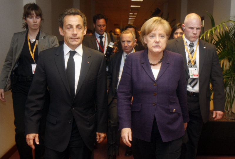 French President Nicolas Sarkozy, second from left, walks with German Chancellor Angela Merkel, second from right, after a meeting on the sidelines of an emergency European Union summit Friday in Brussels.