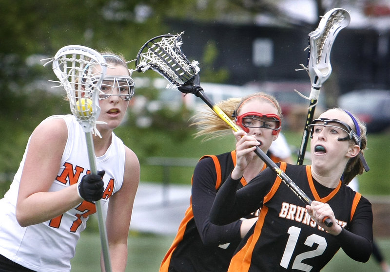 Jill Brady/Staff Photographer Caroline Bowne of North Yarmouth Academy advances the ball Saturday while Leila Mills, right, defends for Brunswick. It was the first-ever matchup between Brunswick, which won the Class A championship last season, and North Yarmouth Academy, the runner-up in Class B.